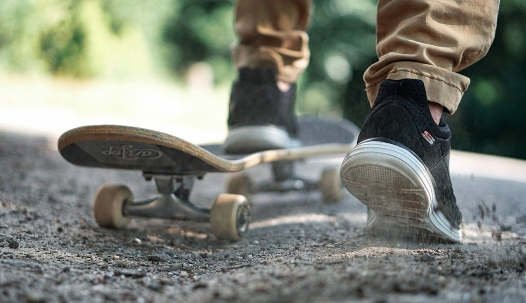 boy on dirt road with skateboard